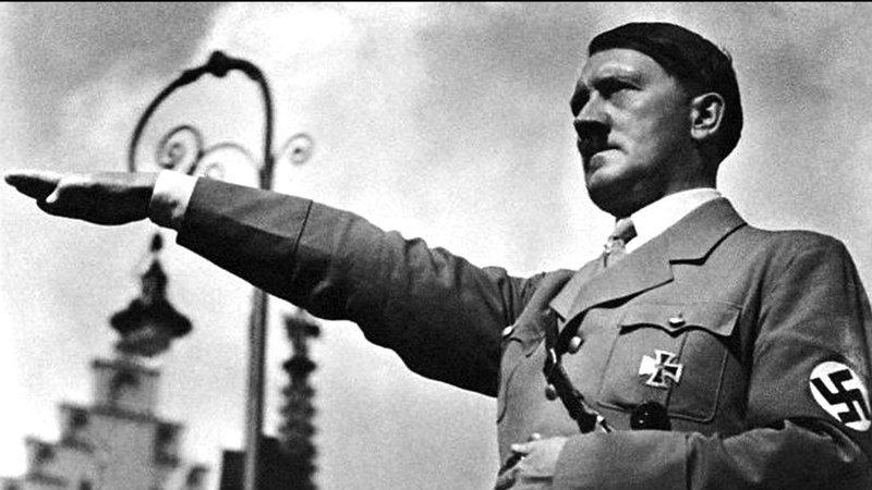 """A náci karlendítés az 1900-as évek pángermán mozgalmában elterjedt """"heil"""" köszöntésből, másrészt egy, tévesen a rómaiaknak tulajdonított gesztus kombinációjából jött létre. A Hitlernek történő engedelmesség jelzésére az 1930-as években vezette be az NSDAP, és kötelező volt a civilek számára"""